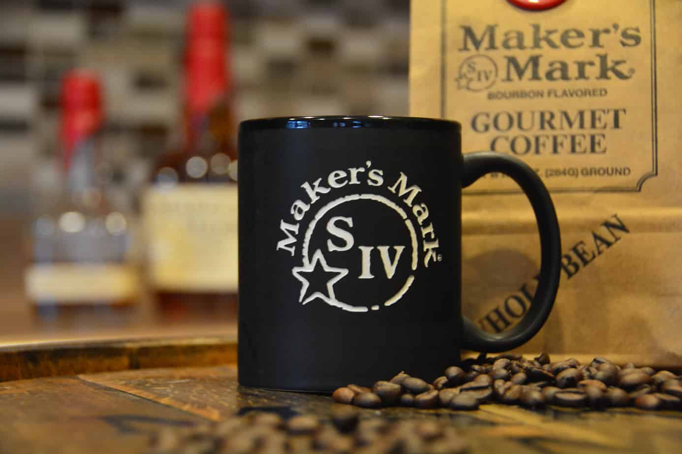 Close up picture of Makers Mark branded mug, next to coffee beans and branded gourmet coffee.